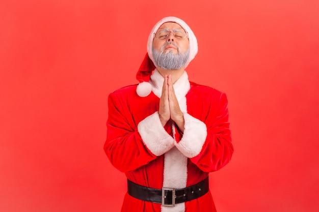 De kerstman kijkt omhoog met de handen in gebed, oprecht zeggend alsjeblieft, verontschuldiging.