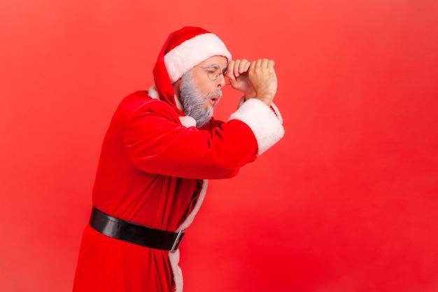 De kerstman kijkt ver weg door een verrekijkergebaar, spioneert met een geschokte verbaasde uitdrukking.