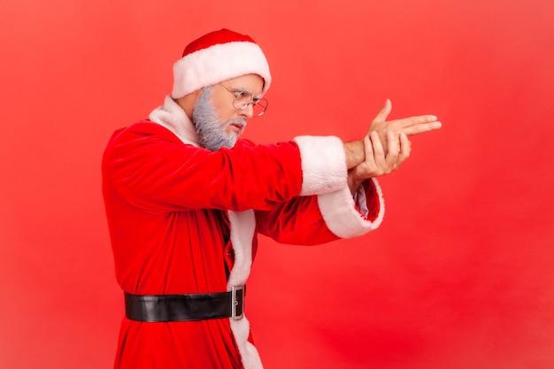 De kerstman kijkt vooruit, wijst handgeweer, schiet met vingerpistool.