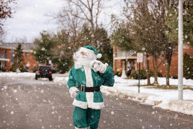 De kerstman komt op kerstavond het huis binnen op het dragen van een zak met kinderen die een cadeau geven die langs de straat loopt tijdens een sneeuwval