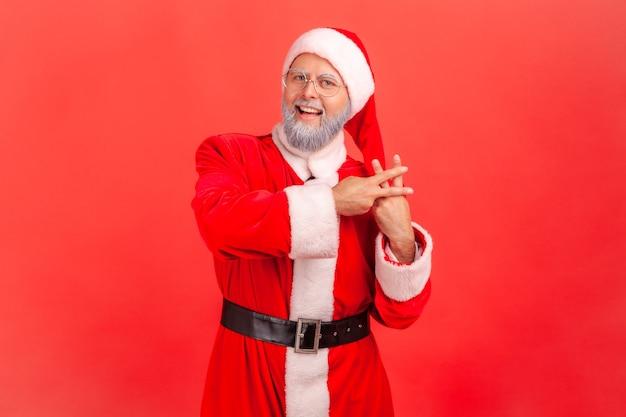 De kerstman kruist zijn vingers om een hashtag-teken te maken en kijkt naar de camera met een brede glimlach.