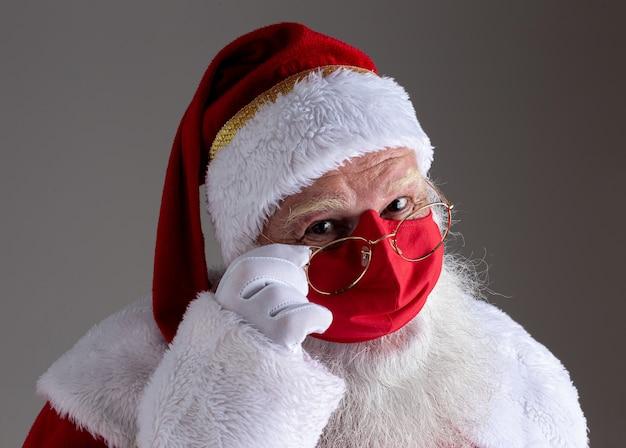 De kerstman lacht achter een rood covid-19 veiligheidsgezichtsmasker. kerst met sociale afstand.
