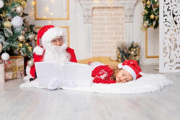 De kerstman leest een boek voor een kindmeisje bij de kerstboom