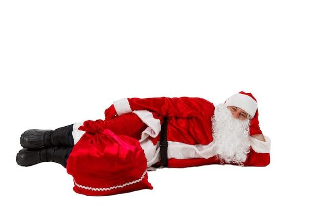 De kerstman ligt met een zak met geschenken.