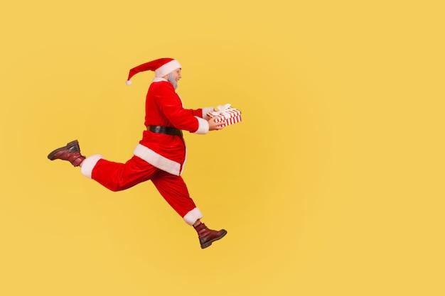 De kerstman loopt met de huidige doos in handen, haast om te feliciteren met het nieuwe jaar.