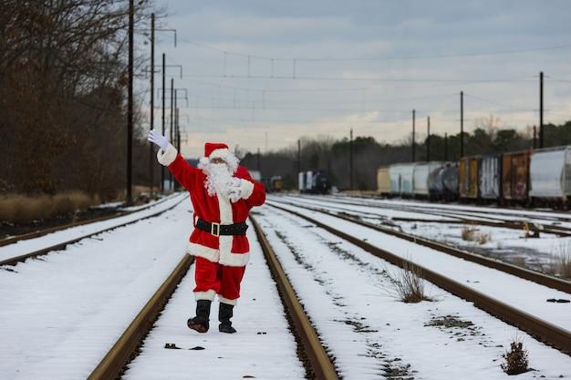 De kerstman loopt op de rai-weg en zwaait met zijn hand op eerste kerstdag bij het dragen van een zak met geschenken