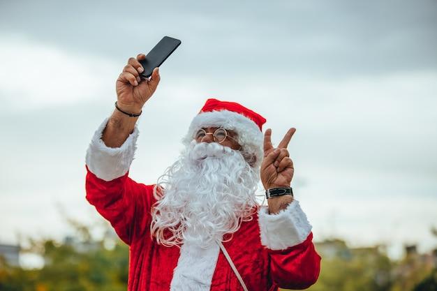 De kerstman maakt een selfie met de mobiel in de ene hand en de andere maakt het symbool van de overwinning. kersttijd