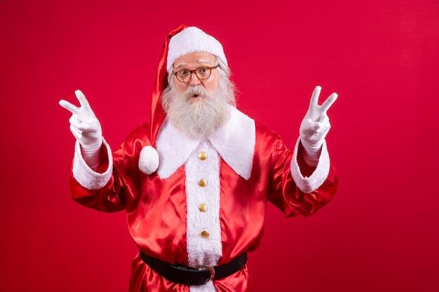 De kerstman maakt het v-teken op de foto. kerstman die een vredes- en liefdesteken en gezichtsuitdrukking maakt. kerstavond, sinterklaas.