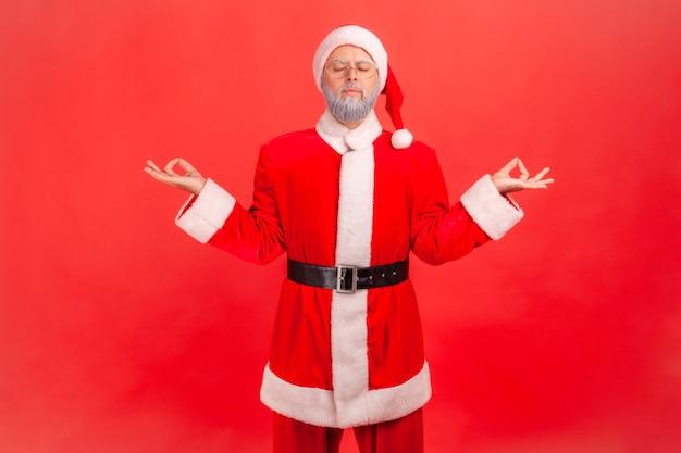 De kerstman mediteert met gesloten ogen, voelt zich kalm, ontspannen met een vredige geest, yogapraktijk.