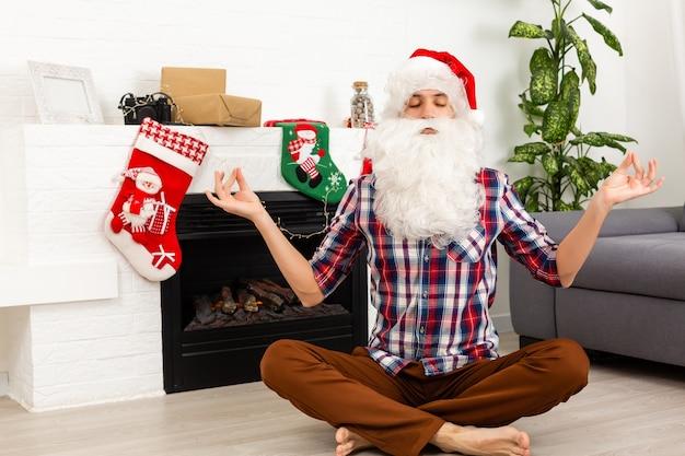 De kerstman mediteert thuis op de achtergrond van de open haard
