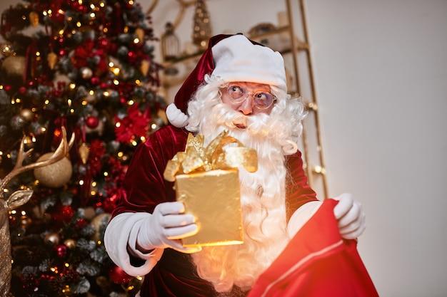 De kerstman met een grote rode zak met cadeaus haast zich om cadeau te brengen aan kinderen.