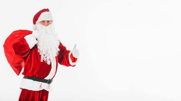 De kerstman met grote zak die duim op gebaar toont