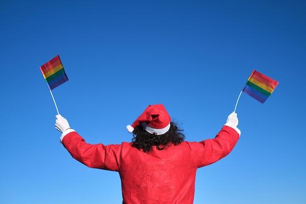 De kerstman met onherkenbare rug heft met zijn handen lgbt-banners naar de hemel