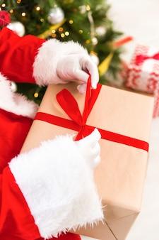 De kerstman overhandigt verpakkende gift met lint