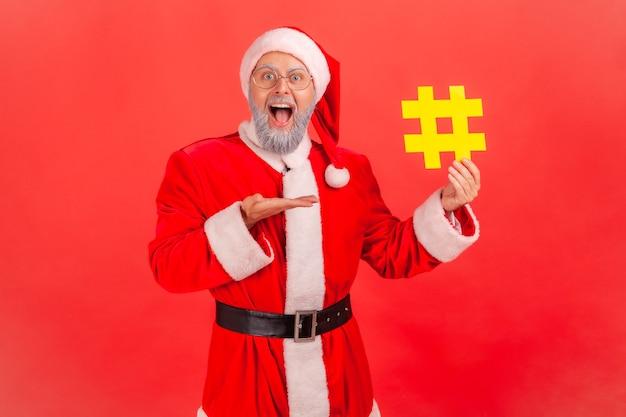 De kerstman presenteert een hashteken, symbool van een viraal bericht sociaal netwerk.