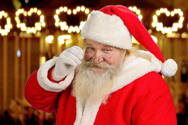 De kerstman raakt zijn bril aan.