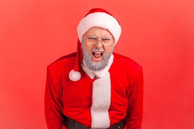 De kerstman schreeuwt luid met agressieve uitdrukking, kijkt naar de camera en schreeuwt.