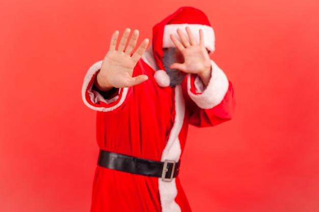 De kerstman sluit de ogen met de hand en strekt de hand uit, beweegt zich in duisternis gezichtsproblemen.