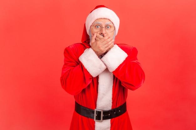 De kerstman sluit zijn mond met zijn handen, bang om te veel te zeggen, verlegenheid.