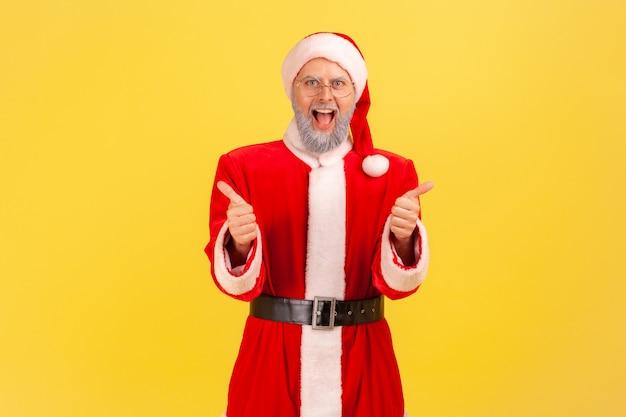 De kerstman staat met open mond, schreeuwt vrolijk en laat zijn duim naar de camera zien.