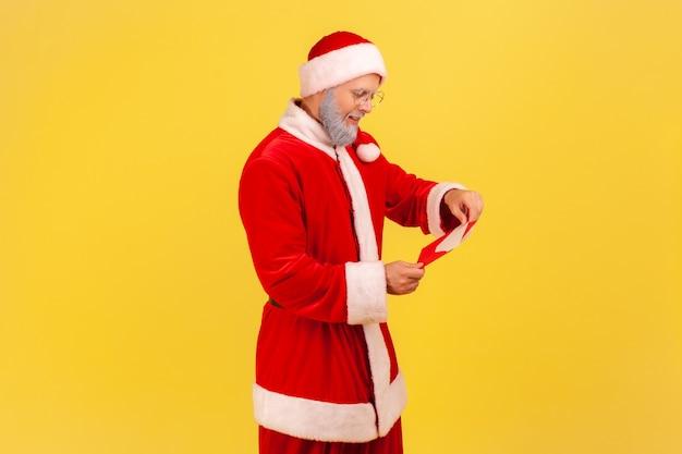De kerstman staat open rode envelop met felicitaties met wintervakantie, brief lezen.