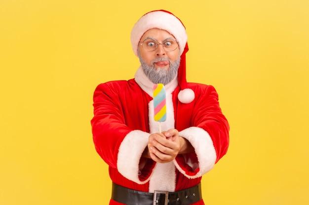 De kerstman steekt suikerachtig ijs uit, kijkt met een grappige uitdrukking, tong uit, hongerig.