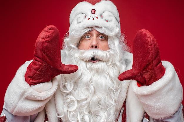 De kerstman toont de grootte van iets door de handen in wanten met een verbaasd gezicht