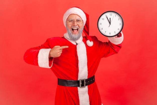 De kerstman toont wijzend op de wandklok, houdt de mond open, geweldige look.