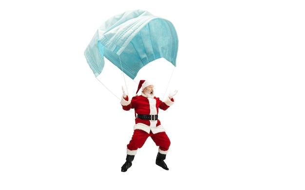 De kerstman vliegt op een enorm gezichtsmasker zoals op een ballon die op een witte achtergrond wordt geïsoleerd