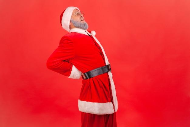De kerstman voelt scherpe pijn in de nieren, rugletsel, beknelde heupzenuw, lijden.