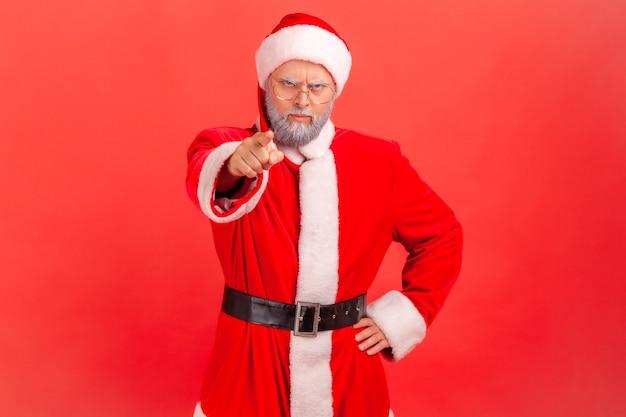 De kerstman wijst naar de camera met een boze uitdrukking en beschuldigt de schuld, wijzend op jou,