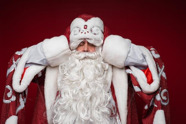 De kerstman wordt moe en grijpt zijn hoofd voor hoofdpijn, gesloten ogen