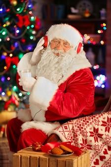 De kerstman zit met een koptelefoon thuis in een comfortabele schommelstoel