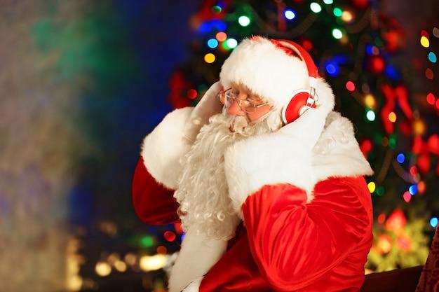 De kerstman zit met een koptelefoon thuis in een comfortabele schommelstoel Premium Foto