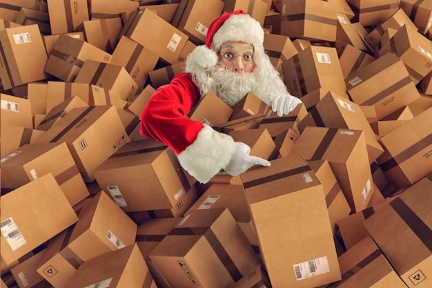 De kerstman zit vol met cadeautjes en dozen voor bezorging