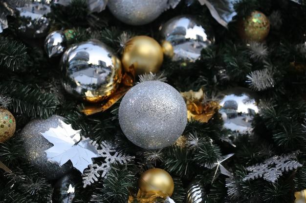 De kerstmisbal hangt op groene achtergrond van de het jaarpartij van de pijnboomboom de nieuwe.