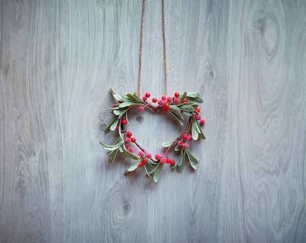 De kerstmiskroon in een vorm van maretak met rode bessen hangt op rustieke geweven houten deur