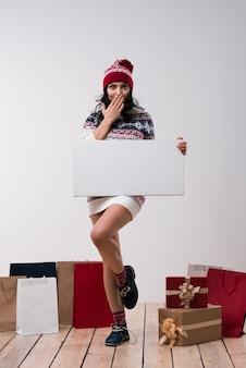De kerstmisvrouw houdt grote witte kaart copyspace