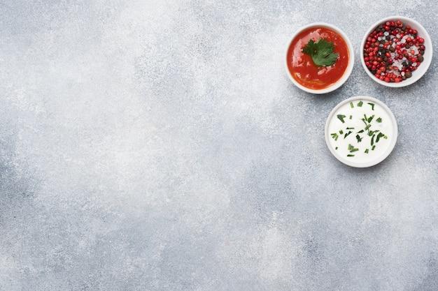 De ketchupmayonaise maakt het zout van de kruidenpeper in platen op een grijze concrete lijst met exemplaarruimte.