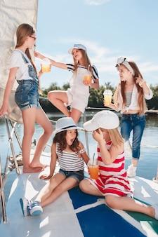 De kinderen aan boord van een zeejacht drinken sinaasappelsap. de tiener of kindmeisjes tegen blauwe hemel openlucht. kleurrijke kleding. concepten voor kindermode, zonnige zomer, rivier en vakantie.
