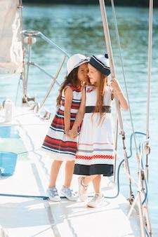 De kinderen aan boord van een zeiljacht. de tiener- of kindmeisjes buiten. kleurrijke kleding. concepten voor kindermode, zonnige zomer, rivier en vakantie.