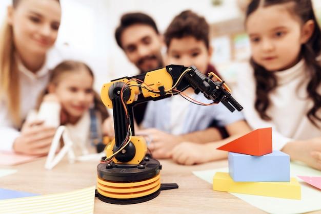 De kinderen kijken naar de robot.
