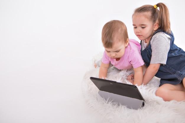 De kinderen kijken naar tekenfilms op de tablet. thuisonderwijs voor meisjes tijdens quarantaine