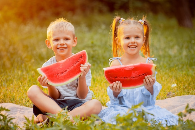 De kinderen op het gazon met plakken van watermeloen in hun dienen de stralen van zonsondergang in