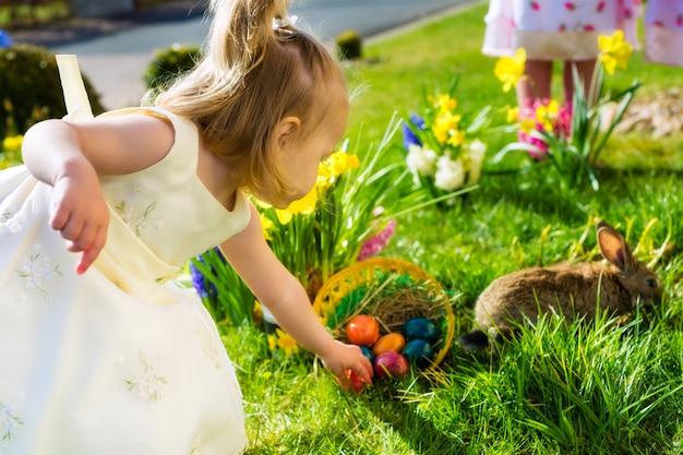 De kinderen op paasei jagen met konijntje