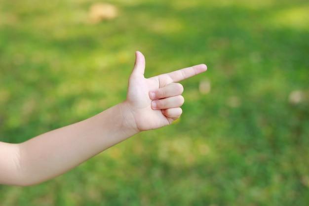 De kinderen overhandigen het richten met wijsvinger of het maken van kanongebaar op onduidelijk beeld groene tuin. de hand van het jonge geitje verschijnt wijsvinger correct of punt.