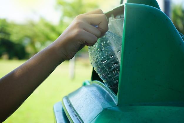 De kinderen overhandigen het werpen van plastic fles aan het vuilnis
