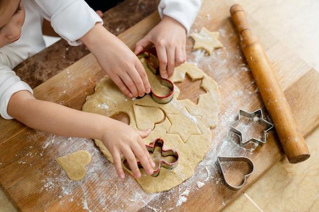 De kinderen snijden koekjes uit het deeg