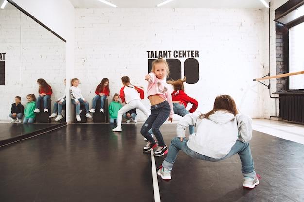 De kinderen zitten op de dansschool. ballet, hiphop, straat, funky en modern dansersconcept