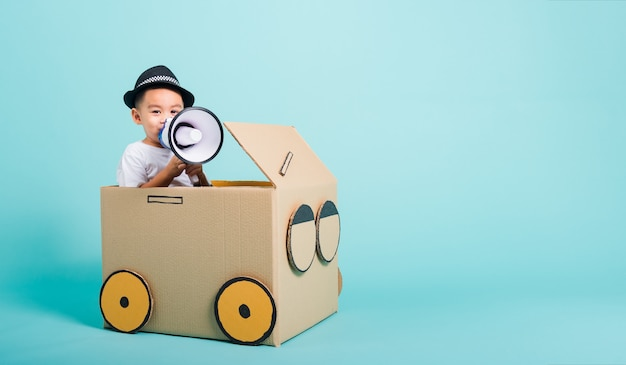 De kinderenjongen glimlachen in het drijven van spelauto creatief door een verbeelding van de kartondoos met megafoon